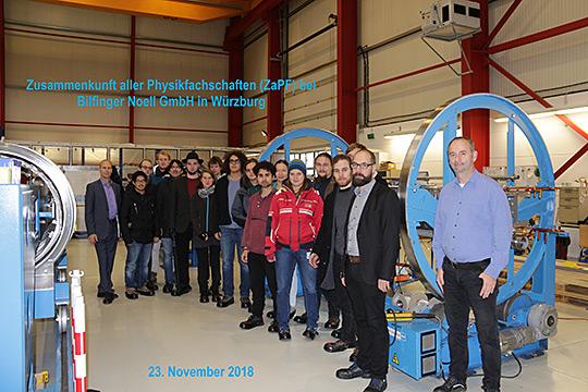 Gruppenfoto vor einer kalten Masse eines SIS100 Dipols-Magneten in der Noell-Fertigungshalle
